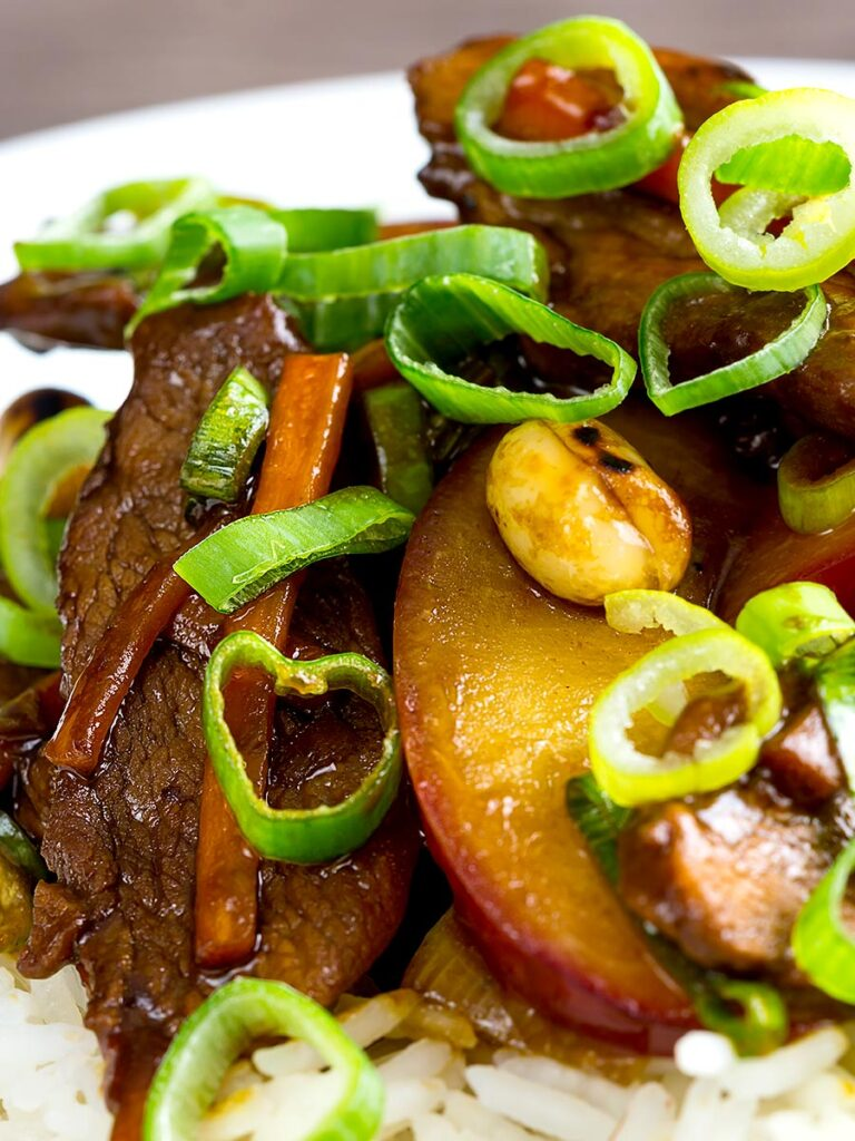 Portrait close up image of Chinese duck stir fry with plums served on white rice