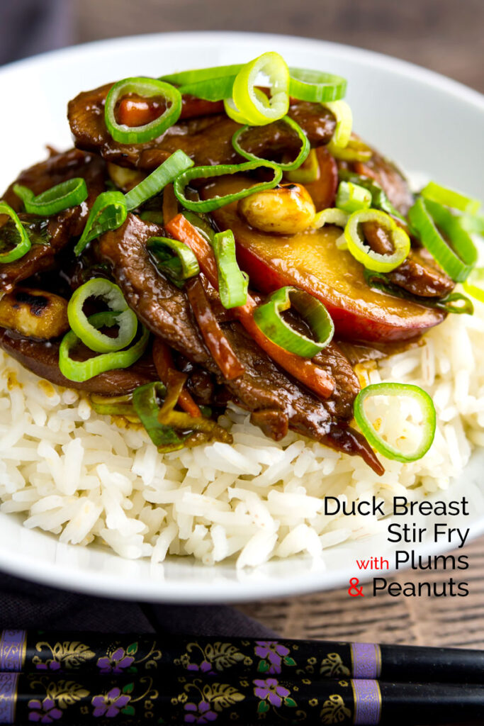 Portrait image of Chinese duck stir fry with plums served on white rice with text overlay