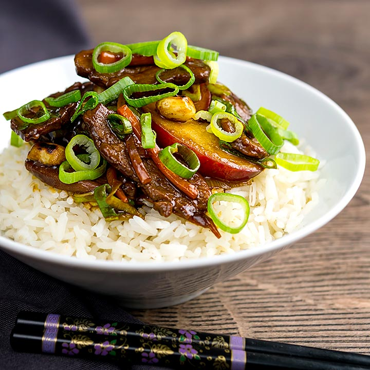 Square image of Chinese duck stir fry with plums served on white rice