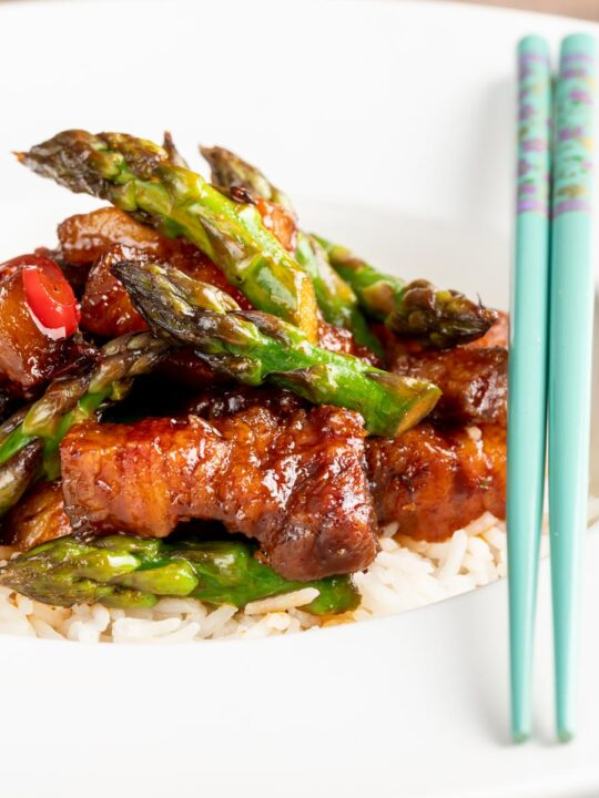 Portrait image of Korean Pork Belly cooked in a spicy coating with asparagus