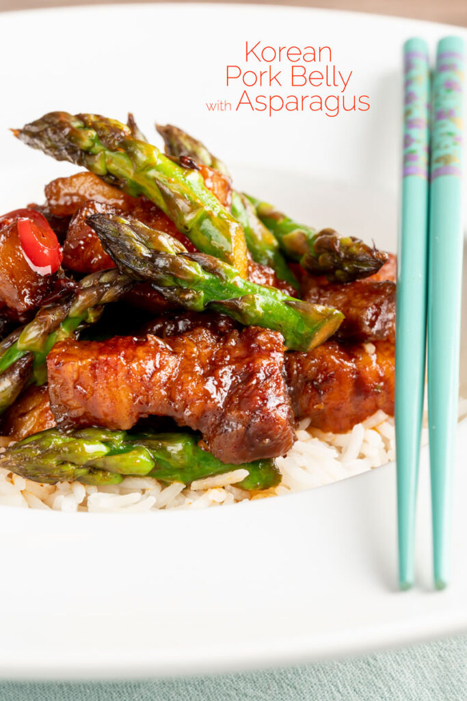 Portrait image of Korean Pork Belly cooked in a spicy coating with asparagus with a text overlay