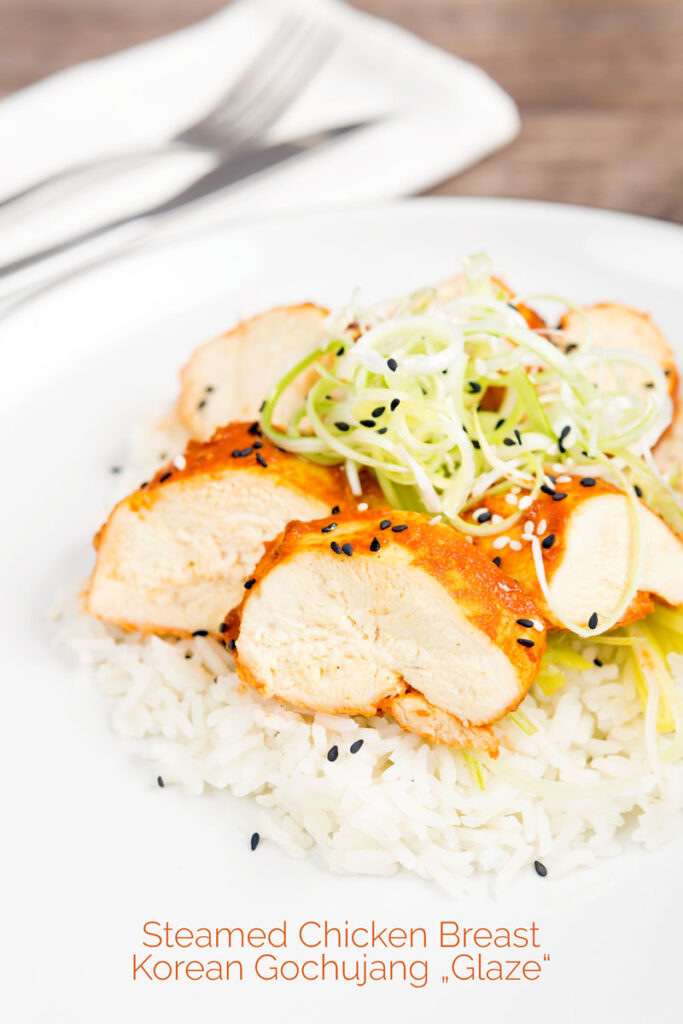 Portrait image of a gouchujang glazed Korean steamed chicken breast served with spring onions with text overlay