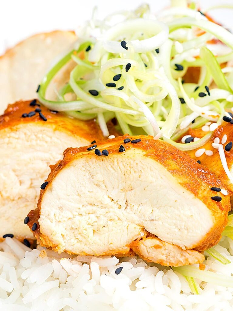 Portrait close up image of a gouchujang glazed Korean steamed chicken breast served with spring onions