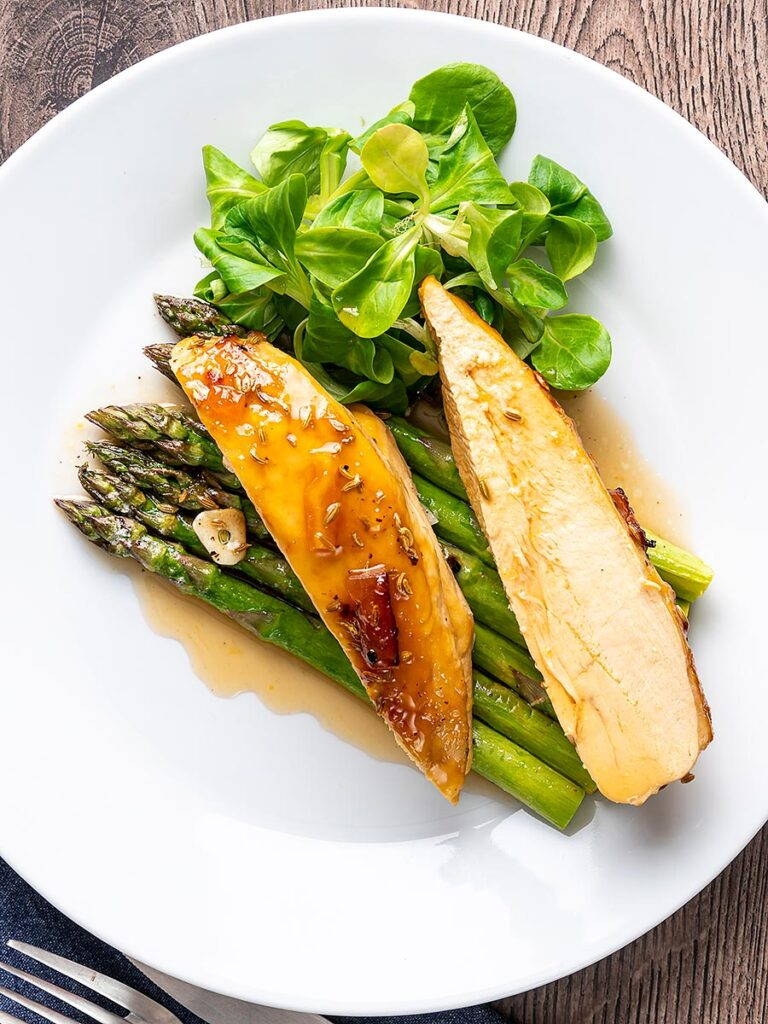 Portrait overhead image of a marmalade glazed chicken breast served with asparagus