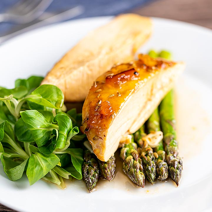 Square image of a marmalade glazed chicken breast served with asparagus