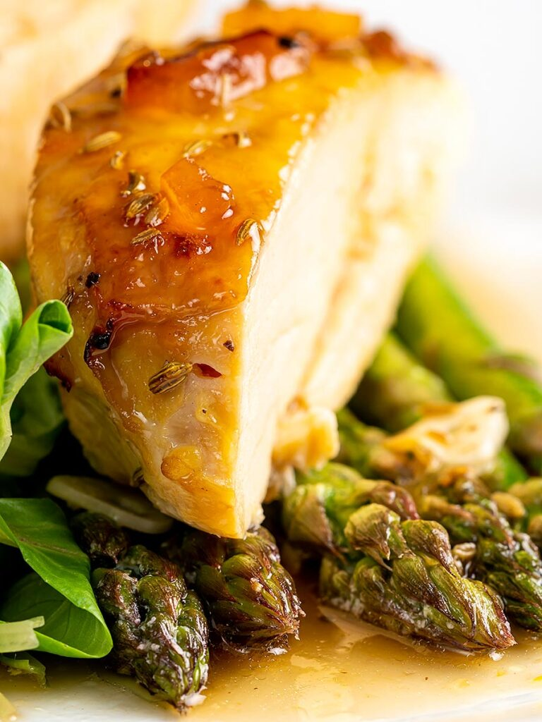 Portrait close up image of a marmalade glazed chicken breast served with asparagus