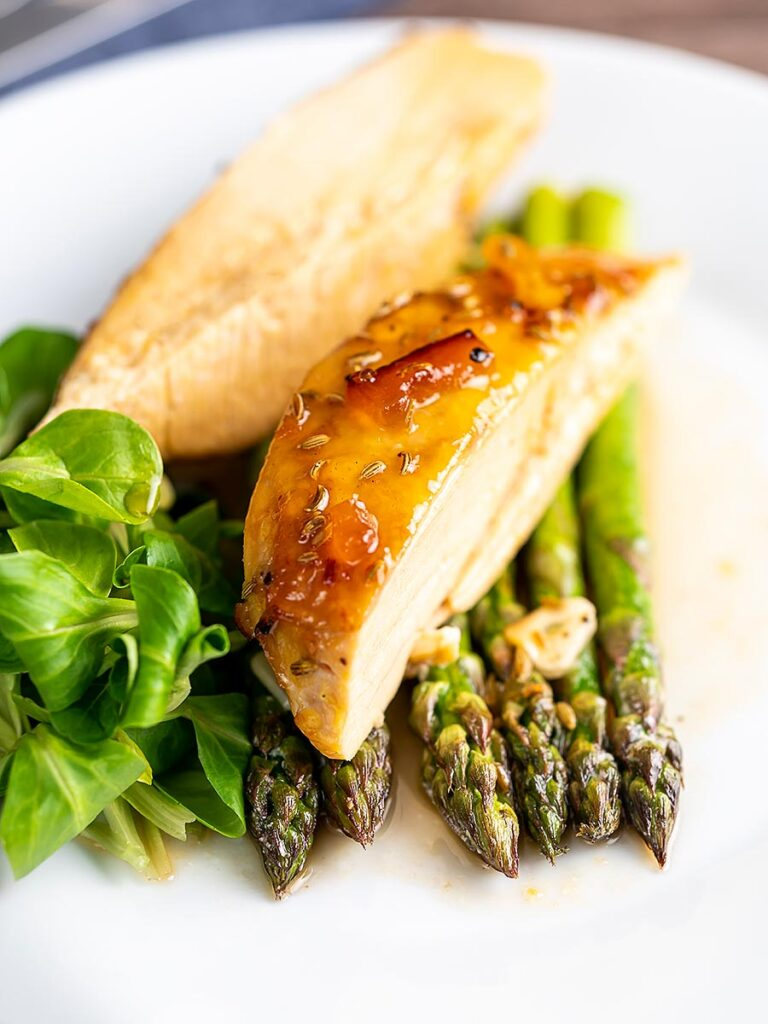Portrait image of a marmalade glazed chicken breast served with asparagus