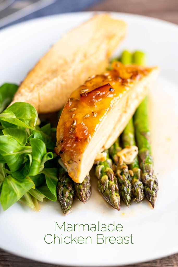 Portrait image of a marmalade glazed chicken breast served with asparagus with text overlay