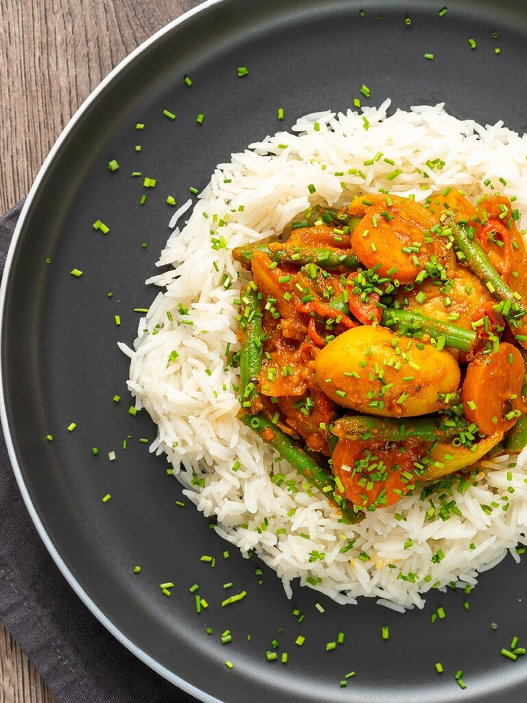 Portrait overhead image of a mixed vegetable karahi curry served on a bed of boiled rice with snipped chives