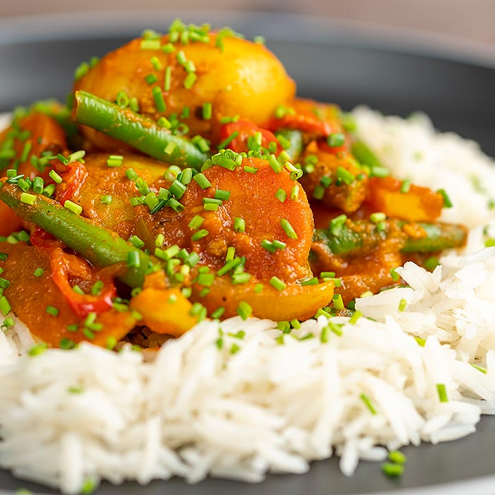 Square image of a mixed vegetable karahi curry served on a bed of boiled rice with snipped chives
