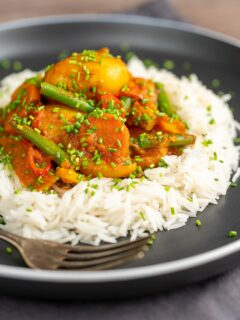 Portrait image of a mixed vegetable karahi curry served on a bed of boiled rice with snipped chives