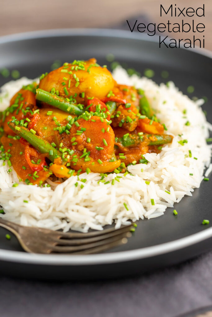 Portrait image of a mixed vegetable karahi curry served on a bed of boiled rice with snipped chives with text overlay