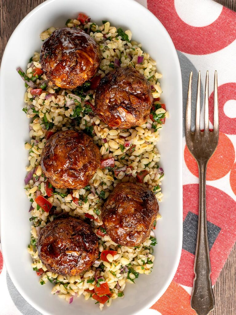 Portrait overhead image of North African influenced meatballs served on a tabbouleh salad in a white long bowl