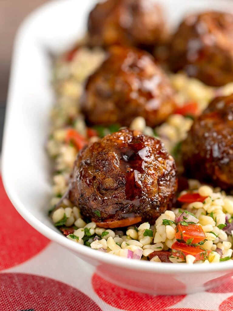 Portrait image of Moroccan influenced meatballs served on a tabbouleh salad in a white long bowl