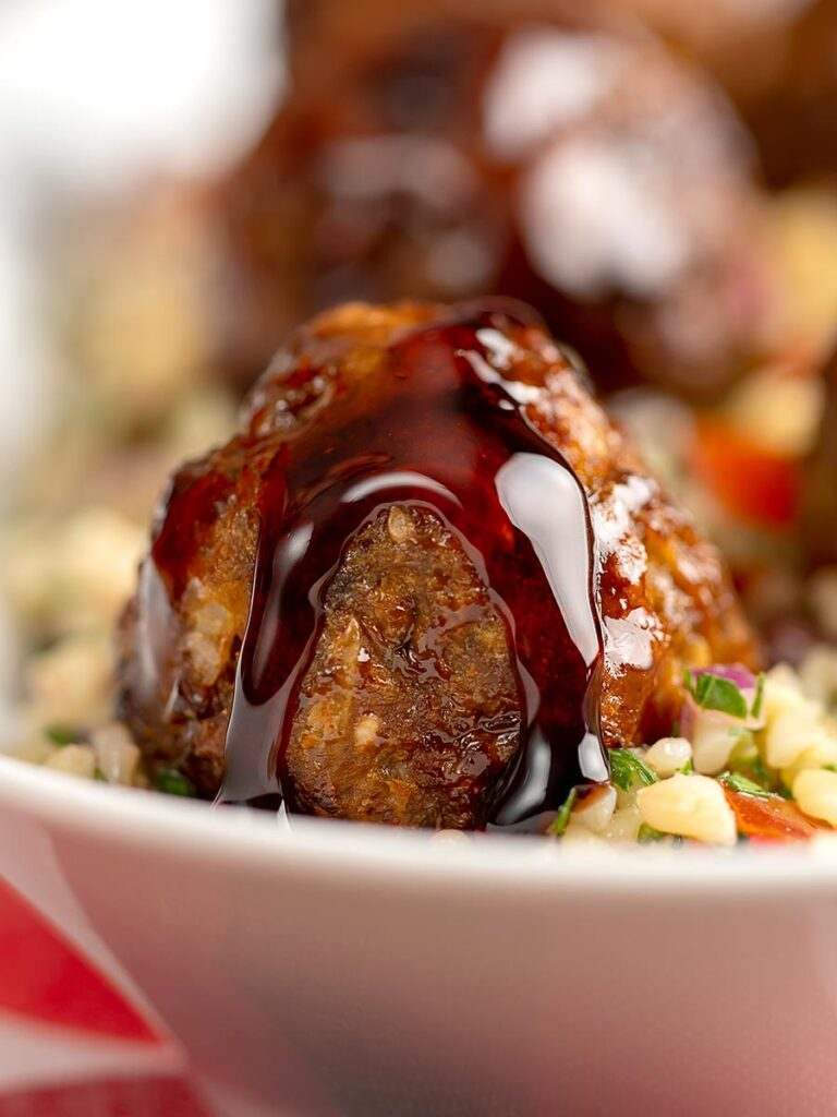 Portrait close up image of North African influenced meatballs with a pomegranate molasses glaze served on a tabbouleh salad