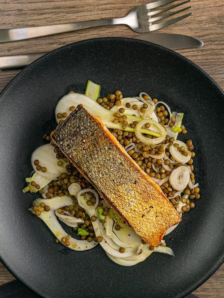 Portrait overhead image of a crispy skinned pan seared salmon fillet served on a black plate with lentils and fennel