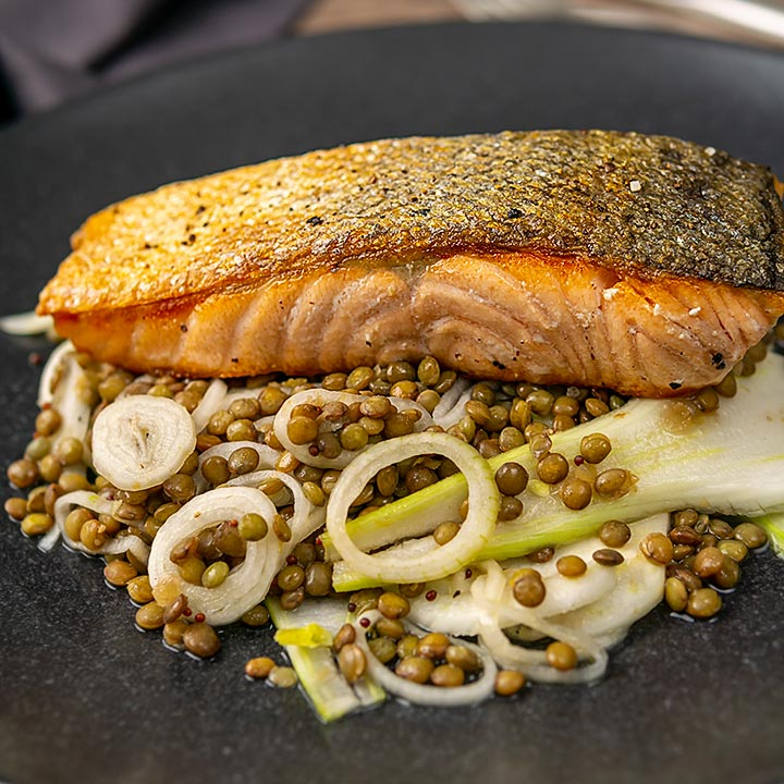 Square image of a crispy skinned pan seared salmon fillet served on a black plate with lentils and fennel