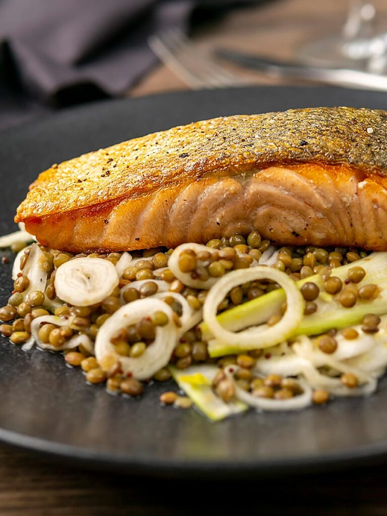 Portrait image of a crispy skinned pan seared salmon fillet served on a black plate with lentils and fennel