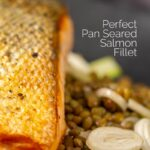 Portrait Close up image of a crispy skinned pan seared salmon fillet served on a black plate with lentils and fennel with text overlay