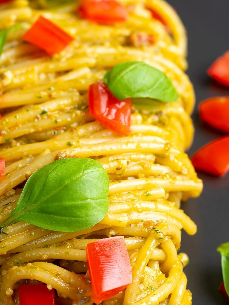 Portrait close up image of pesto alla trapanese served with spaghetti and tomato concasse and fresh basil