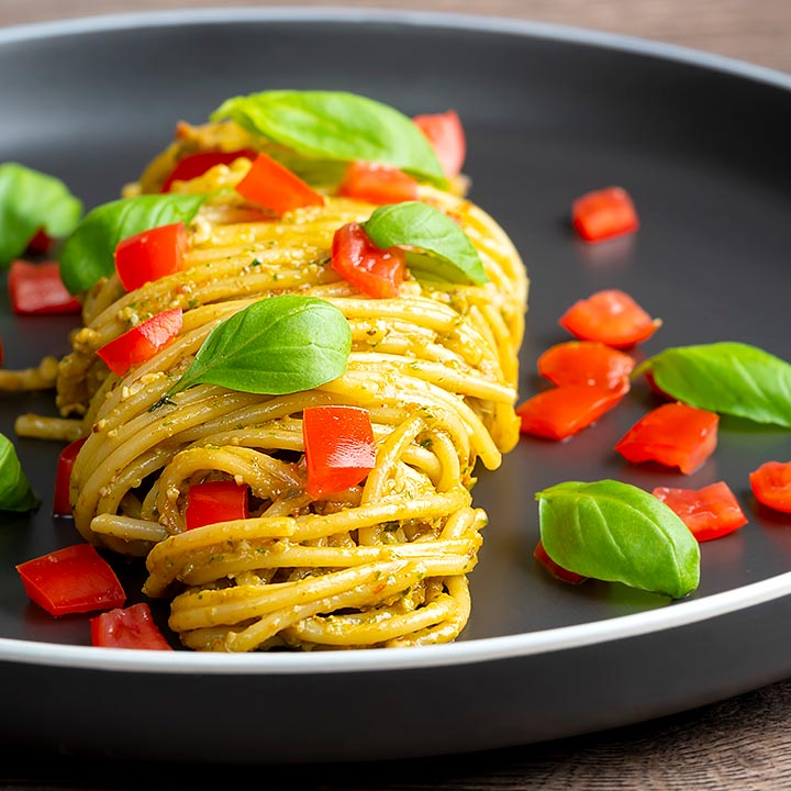 Square image of pesto alla trapanese served with spaghetti and tomato concasse and fresh basil