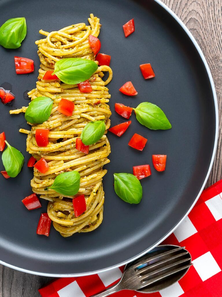 Portrait overhead image of pesto alla trapanese served with spaghetti and tomato concasse and fresh basil