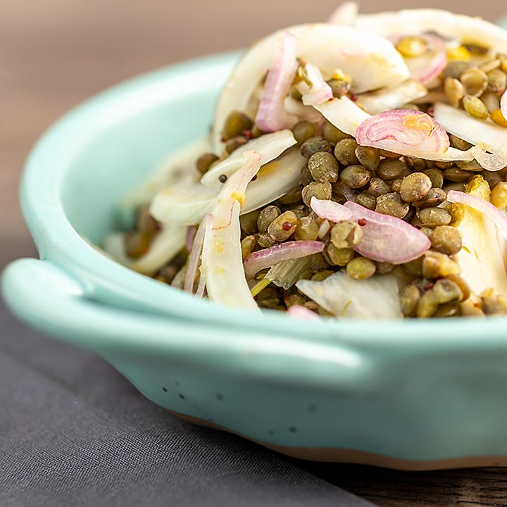 Square image of a pickled fennel salad with puy lentils served in a baby blue bowl