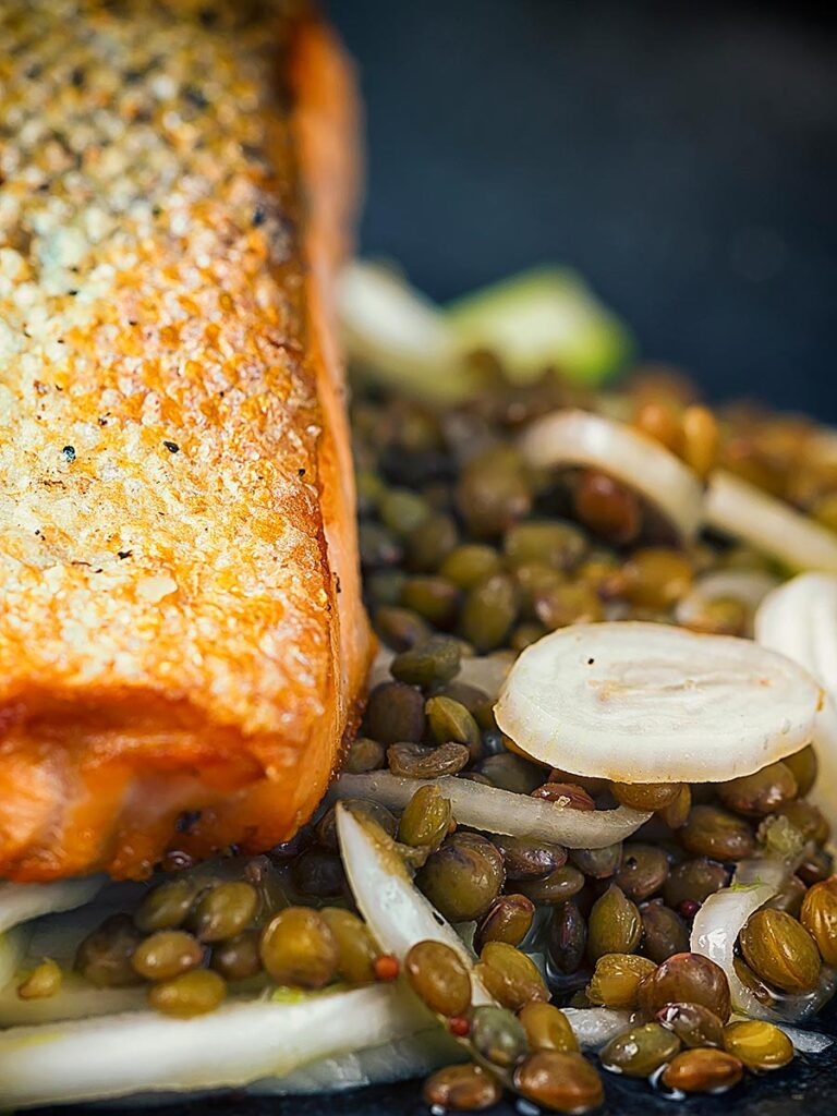 Portrait image of a pickled fennel salad with puy lentils served with pan seared salmon fillet