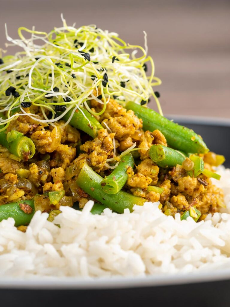 Portrait close up image of a pork mince curry with green beans served with boiled rice and sprouted onion seeds