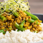 Portrait close up image of a pork mince curry with green beans served with boiled rice and sprouted onion seeds with text overlay
