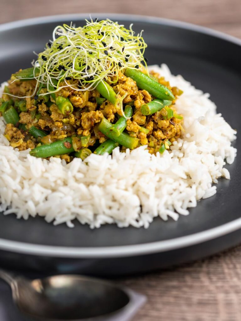 Portrait image of a pork mince curry with green beans served with boiled rice and sprouted onion seeds on a black plate