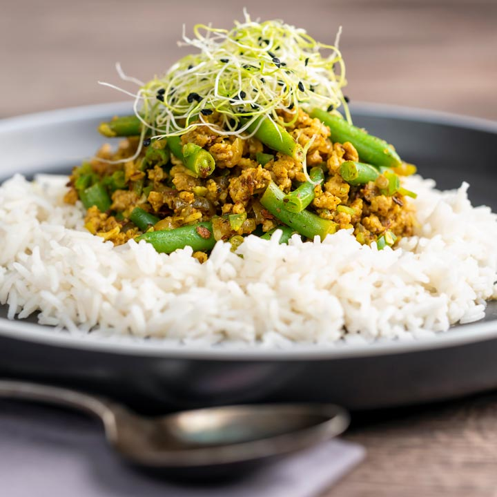 Square image of a pork mince curry with green beans served with boiled rice and sprouted onion seeds on a black plate