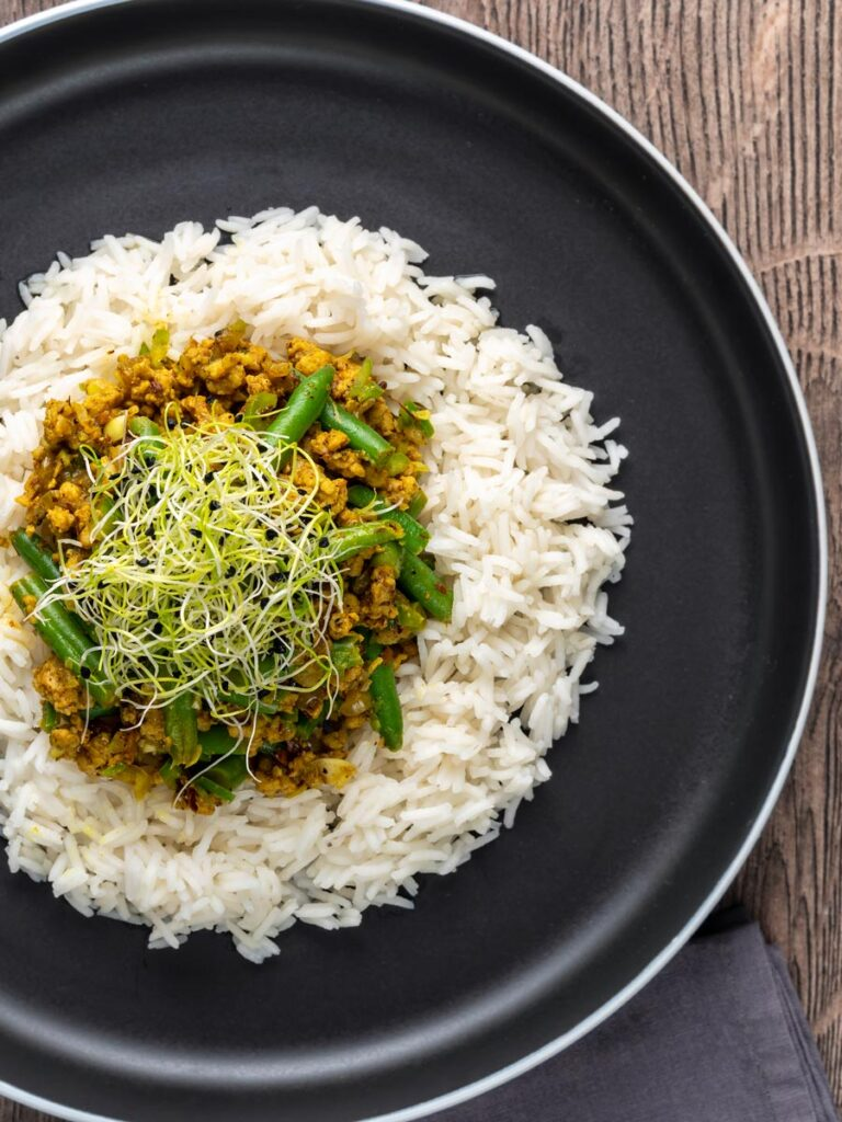 Portrait overhead image of a pork mince curry with green beans served with boiled rice and sprouted onion seeds on a black plate