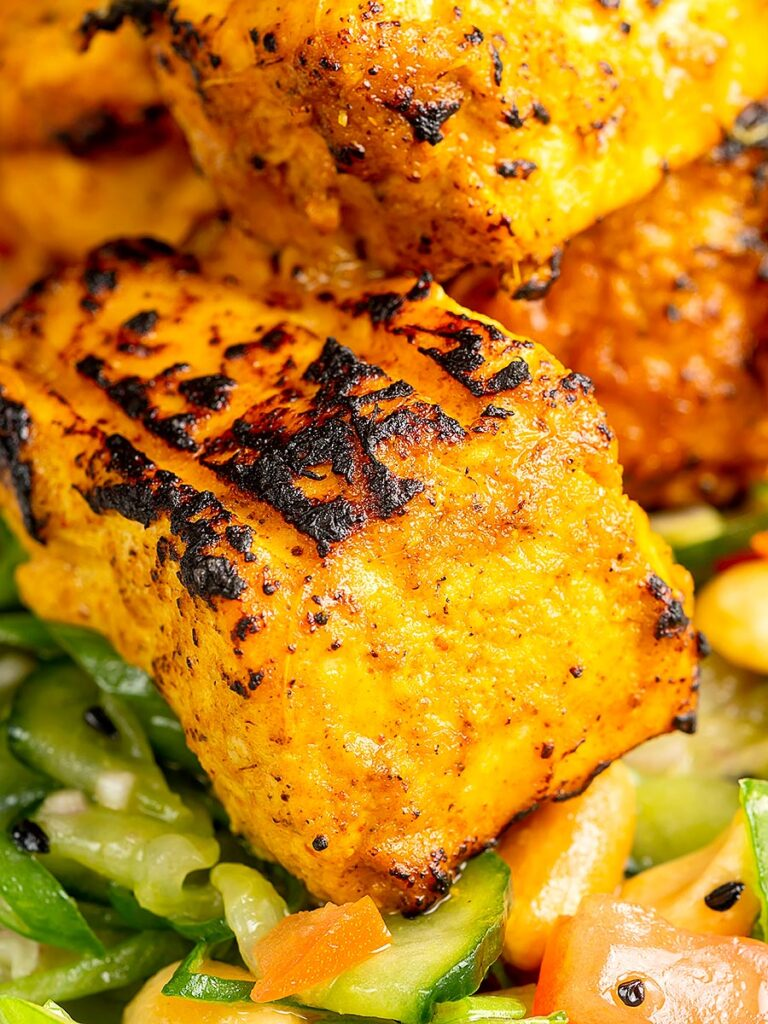 Close up portrait image of grilled salmon tikka served on a cucumber salad