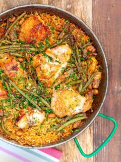 Portrait image of a traditional paella recipe featuring rabbit and chicken served in a paella pan