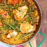 Portrait image of a traditional Valencian paella featuring rabbit and chicken served in a paella pan with text overlay