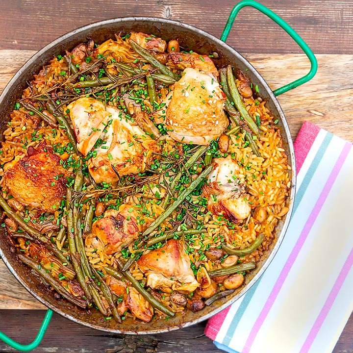 square overhead image of a traditional Valencian paella featuring rabbit and chicken served in a paella pan