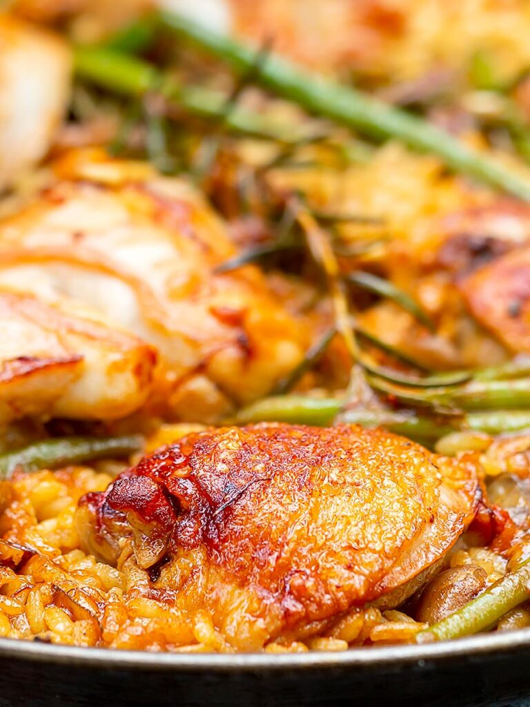 Portrait close up image of a traditional Valencian paella featuring rabbit and chicken