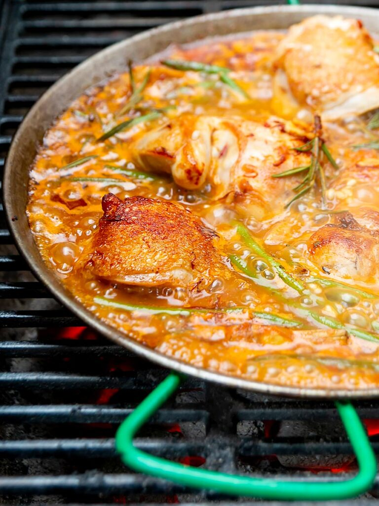 Portrait image of a traditional Valencian paella featuring rabbit and chicken being cooked on a BBQ