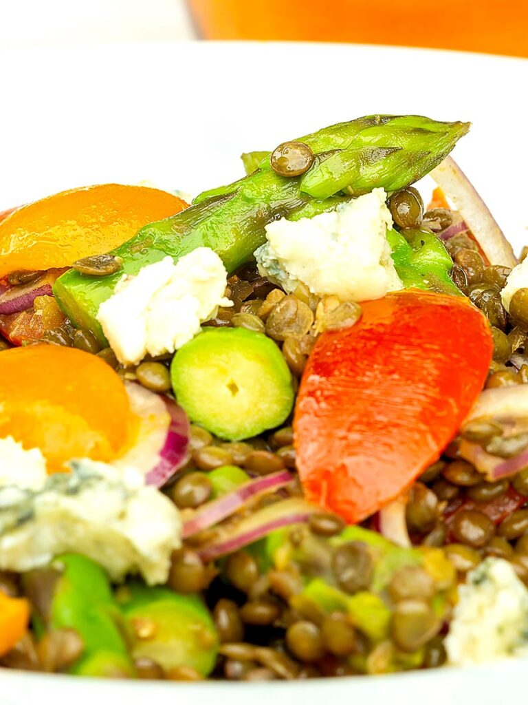 Portrait close up image of an asparagus salad with lentils, blue cheese and tomatoes