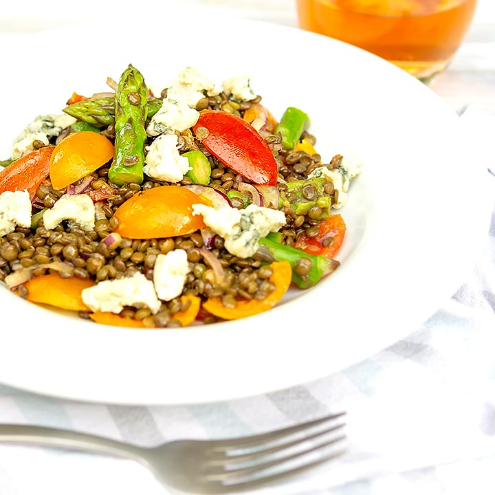 Square image of an asparagus salad with lentils, blue cheese and tomatoes served in a white bowl