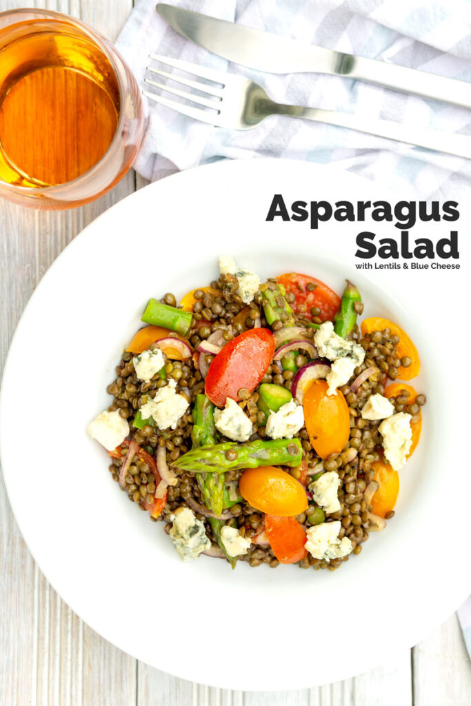 Square overhead image of an asparagus salad with lentils, blue cheese and tomatoes served in a white bowl with text overlay