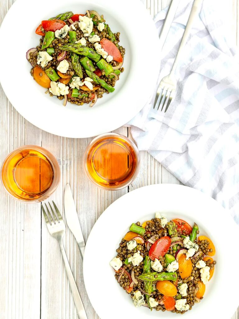 portrait overhead image of an asparagus salad with lentils, blue cheese and tomatoes served in two white bowls served with a glass of wine