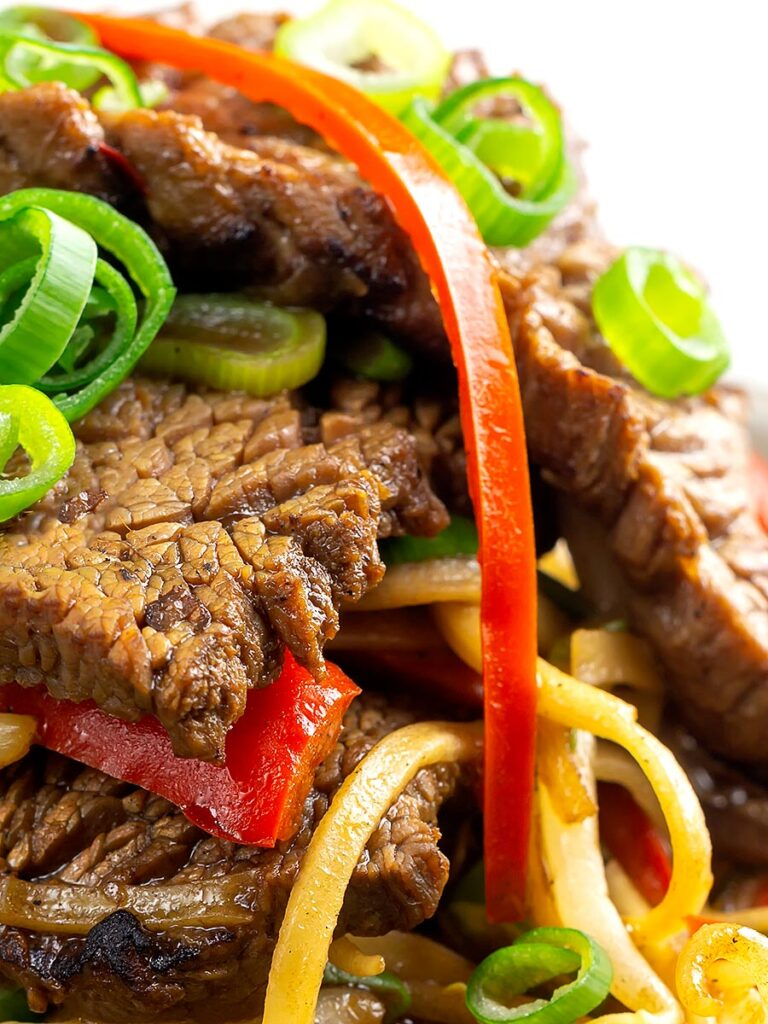Portrait close up image of a beef stir fry with noodles, chilli and spring onions