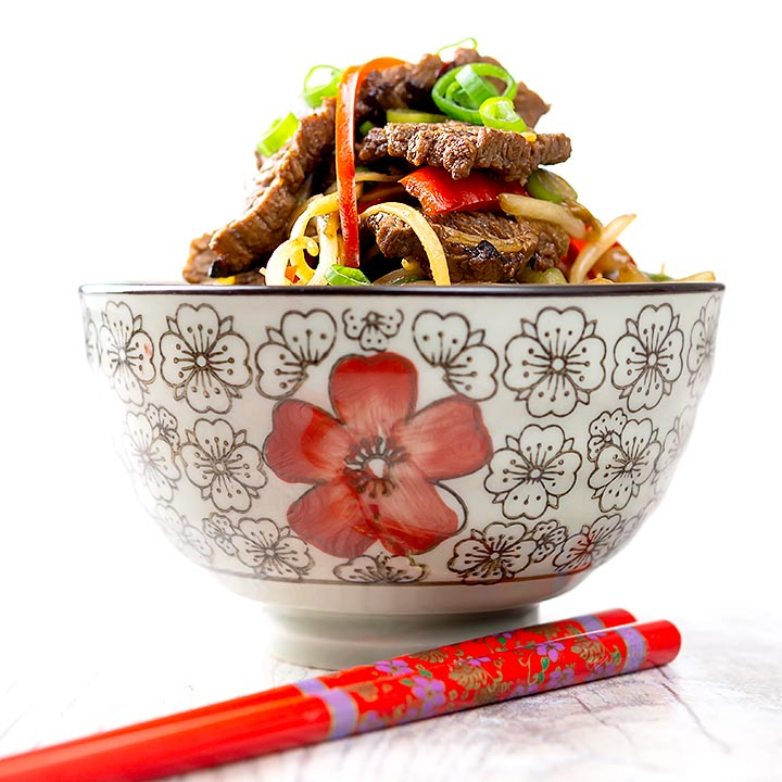 Square image of a beef stir fry with noodles, chilli and spring onions served in a bowl decorated in an Asian style