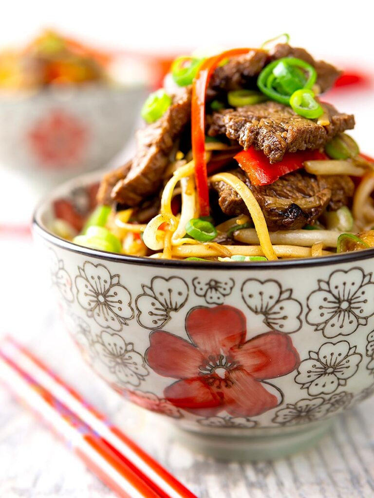 Portrait image of a beef stir fry with noodles, chilli and spring onions served in a bowl decorated in an Asian style