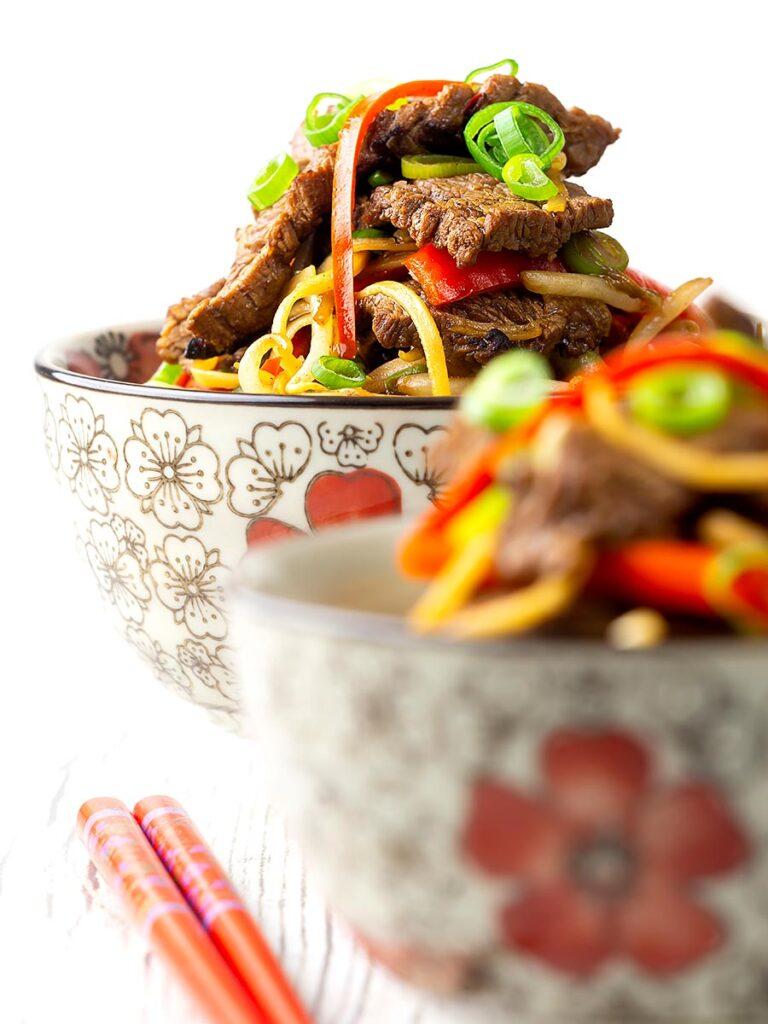 Portrait image of a beef stir fry with noodles, chilli and spring onions