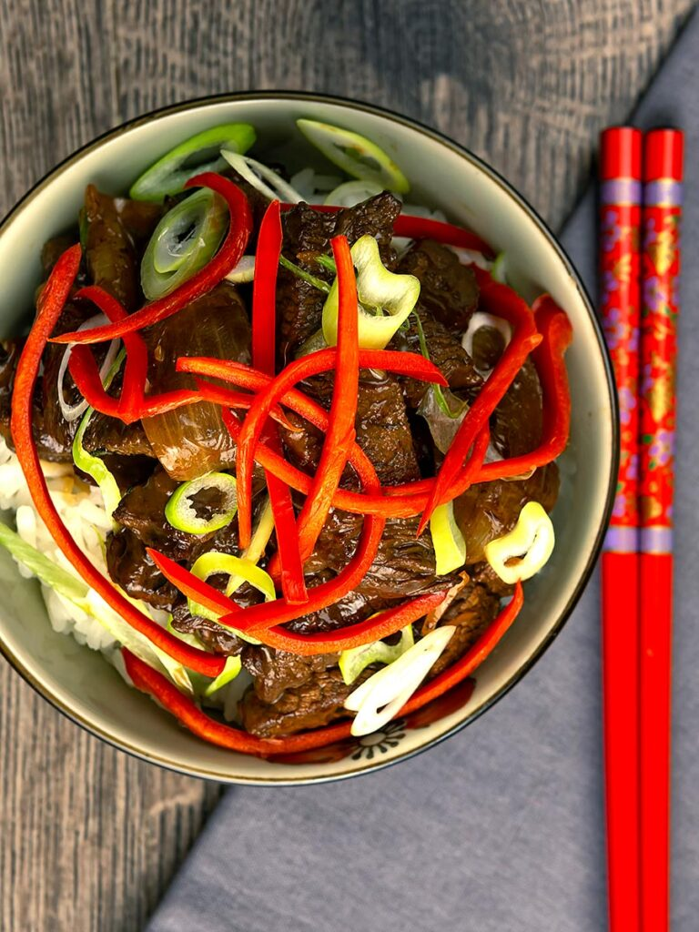Portrait overhead image of Beef in oyster sauce stir fry served in a bowl garnished with chilli and spring onion
