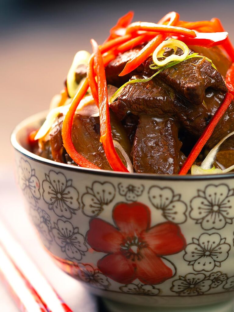 Portrait image of Beef in oyster sauce stir fry served in a bowl decorated with an Asian flower design garnished with chilli and spring onion.