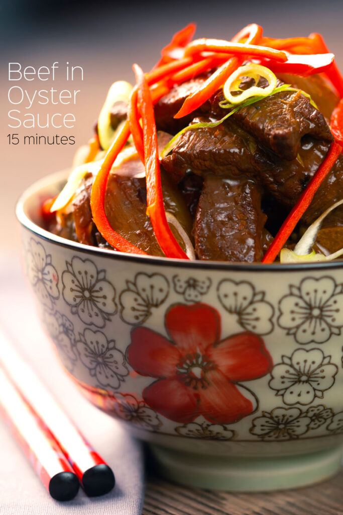 Portrait image of Beef in oyster sauce stir fry served in a bowl decorated with an Asian flower design garnished with chilli and spring onion with text overlay.